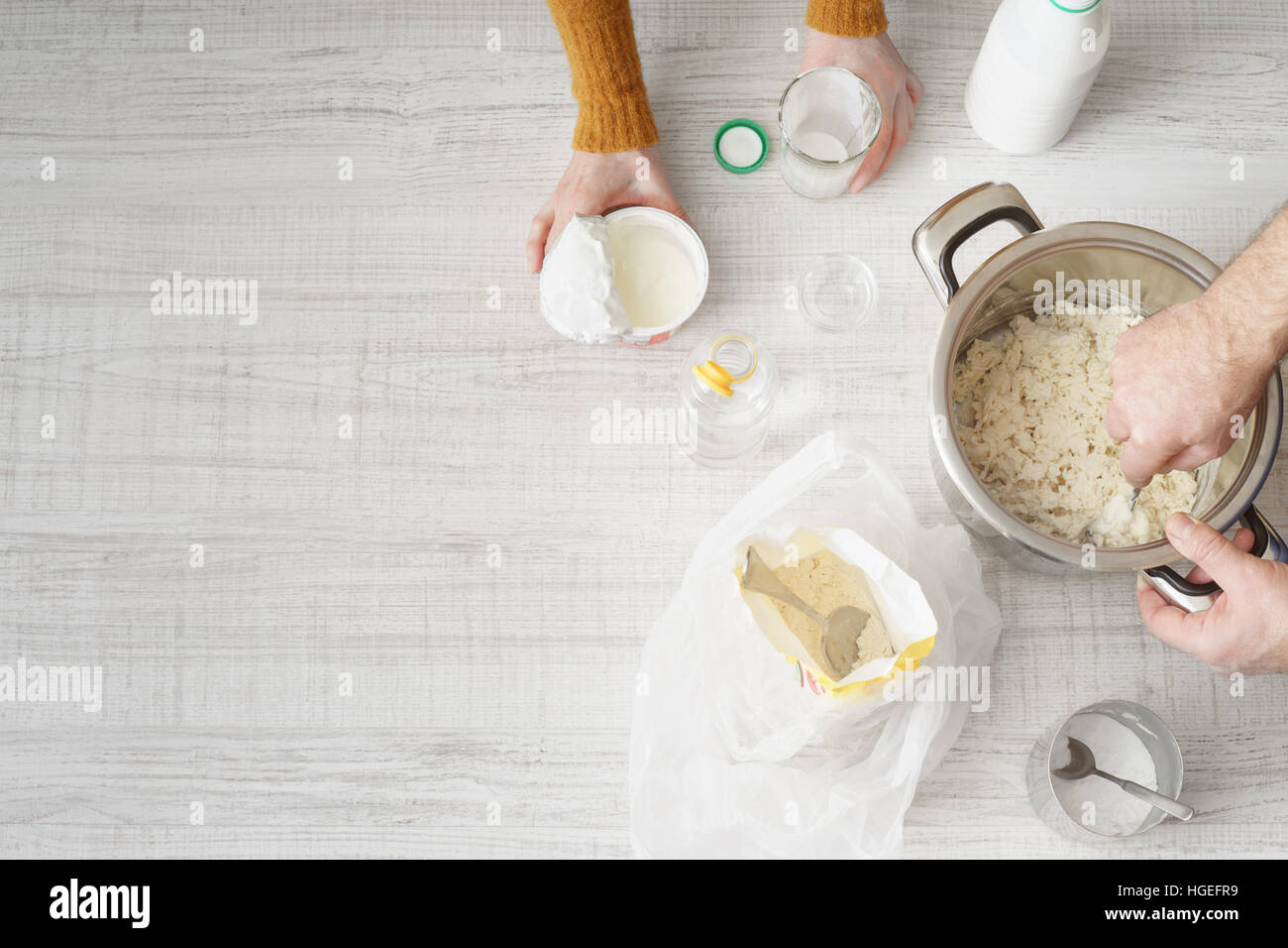 Man and woman makes the dough in the pan on the wooden table horizontal Stock Photo