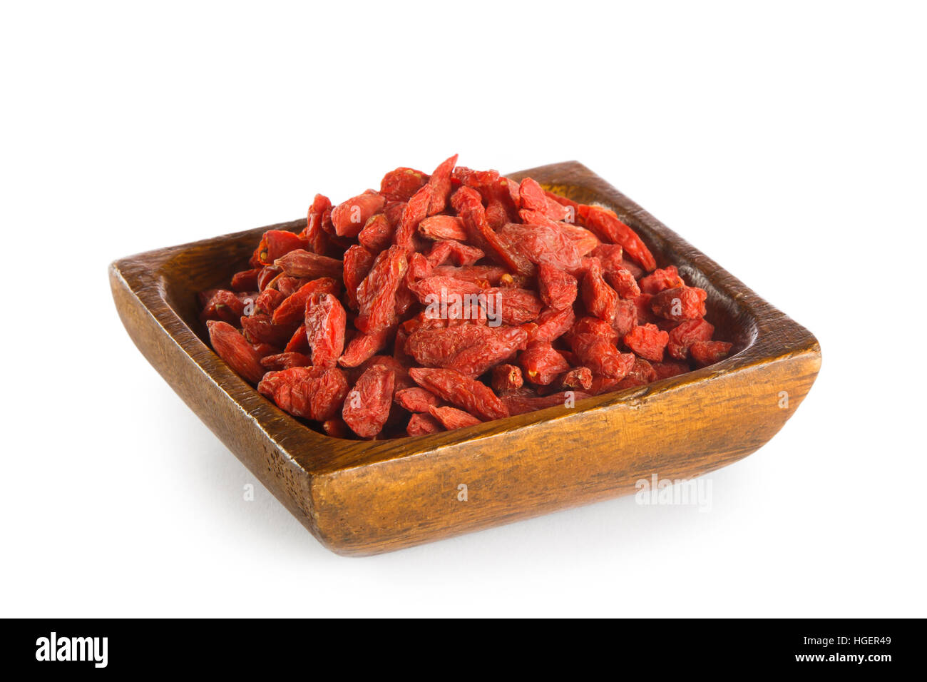 Goji berries in wooden bowl isolated on white background. Superfood - Stock Image