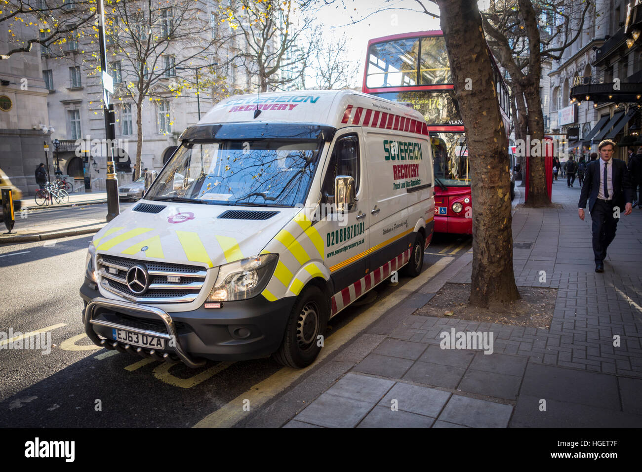 Sovereign Recovery van fixing a broken down red London bus in Covent Garden, London, UK - Stock Image