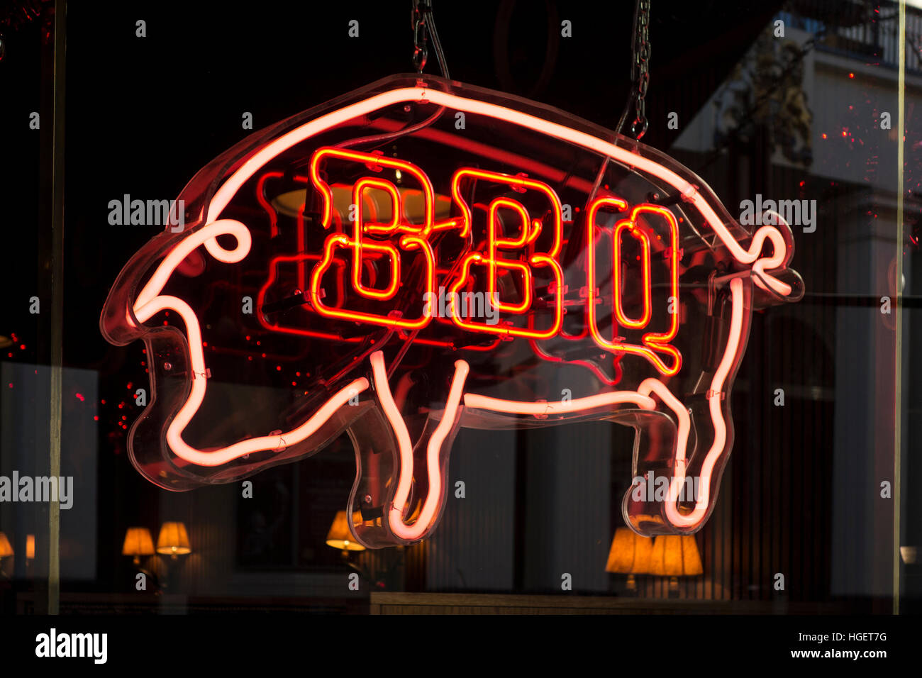 Red BBQ neon restaurant cafe sign in the shape of a pig - Stock Image