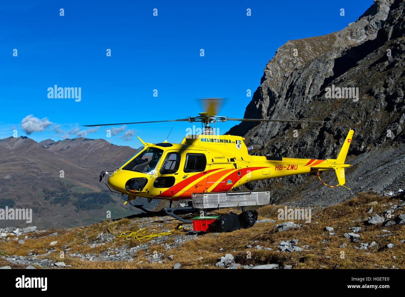 Helicopter Eurocopter AS350 Ecureuil of Heli Bernina AG on a mountainous landing place, Val Lischana, Graubunden, - Stock Image