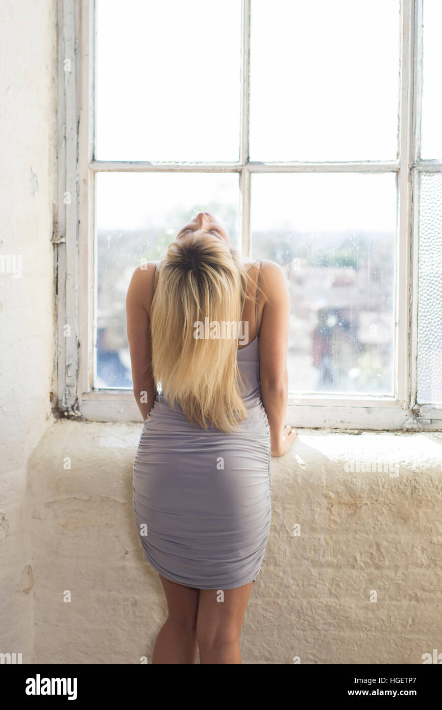 Rear view of a blond woman standing by the window - Stock Image