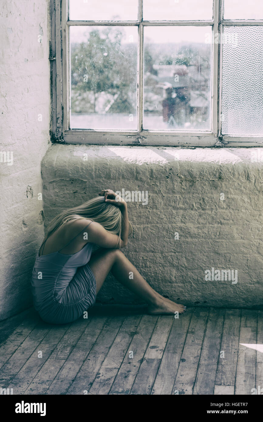 Depressed woman sat on the floor hiding face with hands by the window - Stock Image