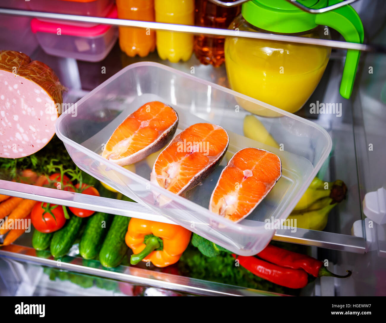 Raw Salmon steak in the open refrigerator - Stock Image