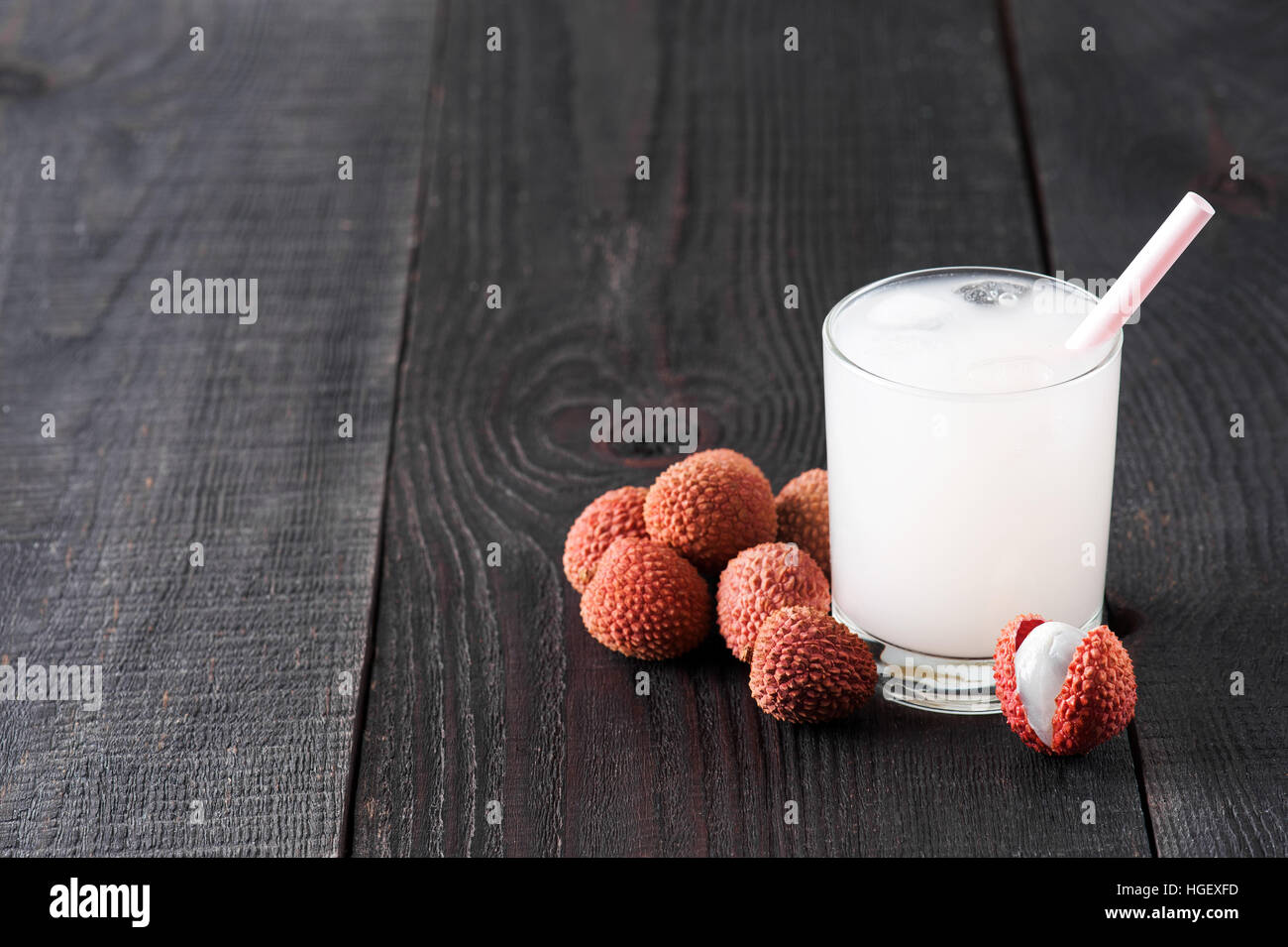 Glass of cold lychee juice on the old wooden table - Stock Image