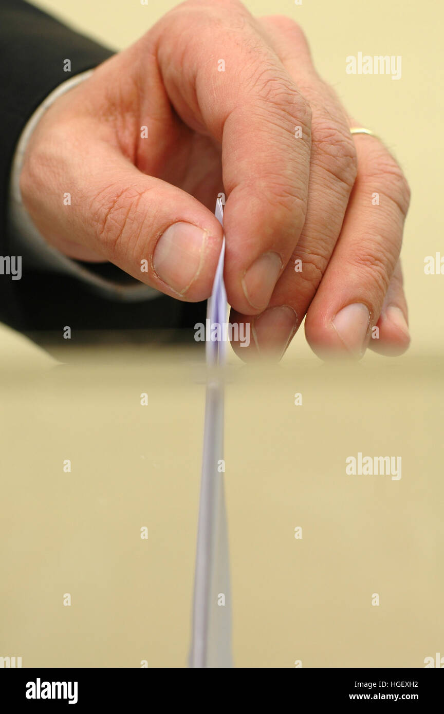 Image of a ballot box and hand putting a blank ballot inside,elections, voting concept - Stock Image