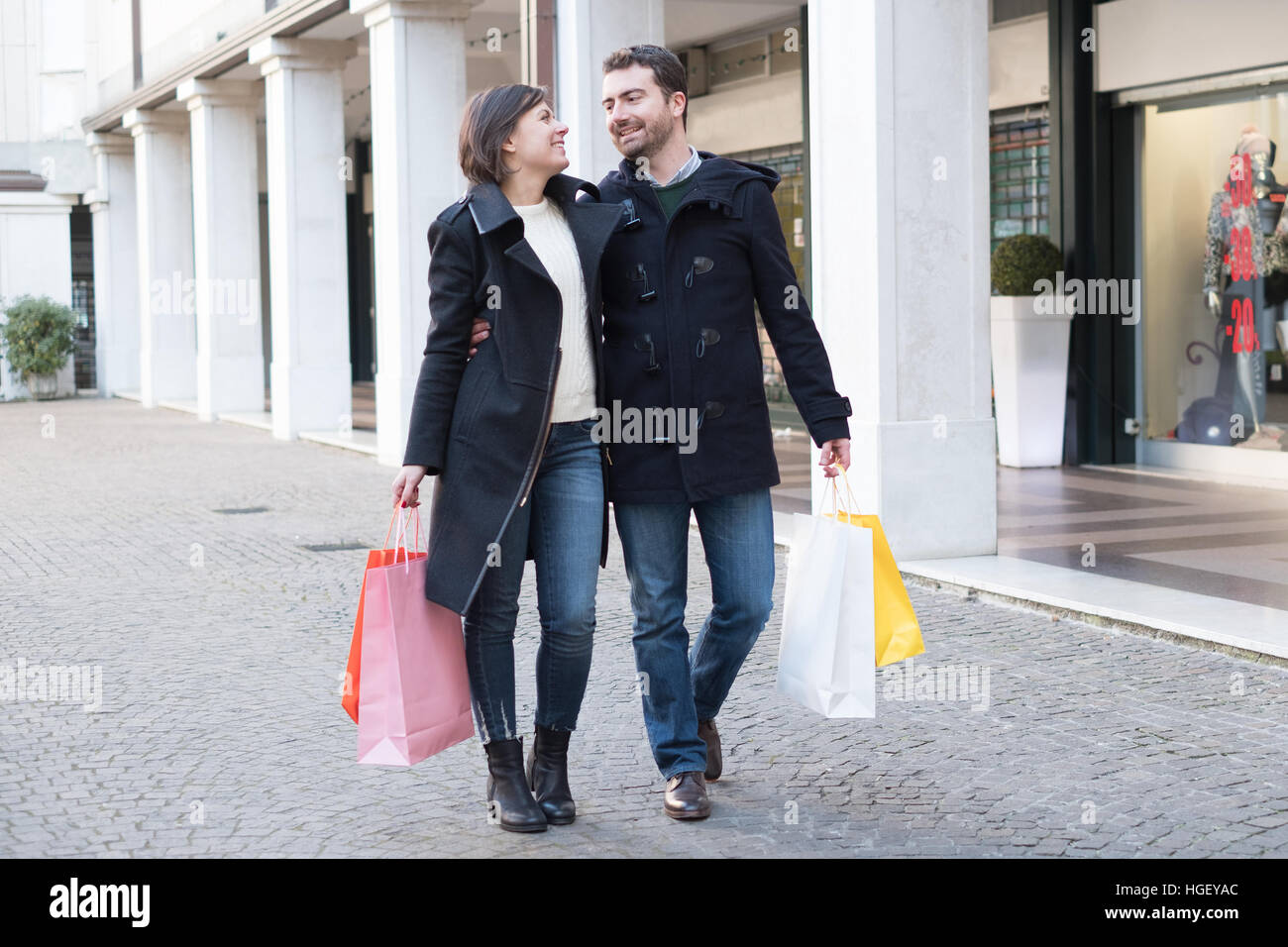 Couple in shopping time walking in the city street - Stock Image