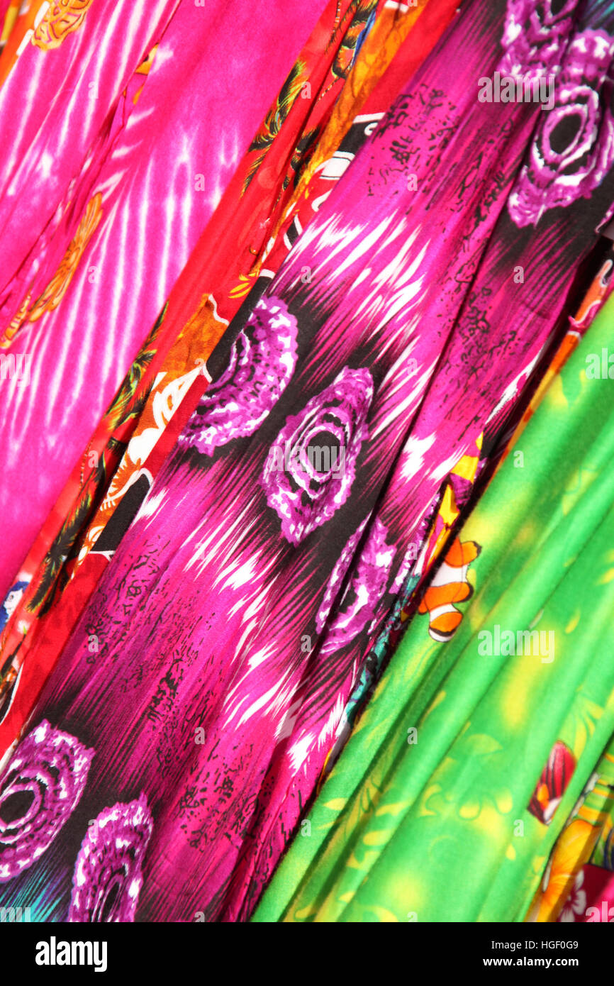 Bright multi colored printed fabrics with a Caribbean or Hawaiian beach style. Stock Photo