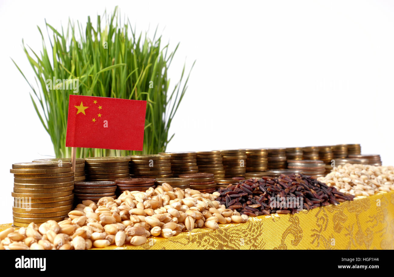 People's Republic of China flag waving with stack of money coins and piles of wheat and rice seeds - Stock Image
