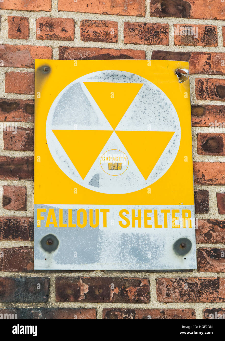 Yellow nuclear radioactive fallout shelter sign on a brick wall, USA - Stock Image