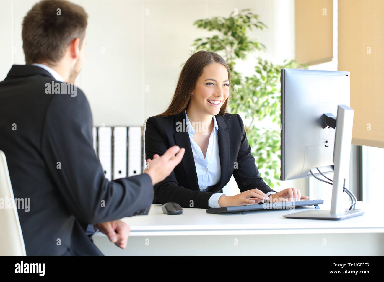 Agent attending to a client introducing data in a desktop computer at office - Stock Image