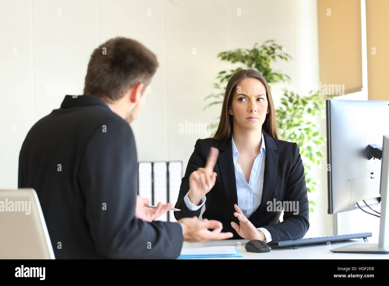 Boss denying something saying no with a finger gesture to an upset employee in her office - Stock Image