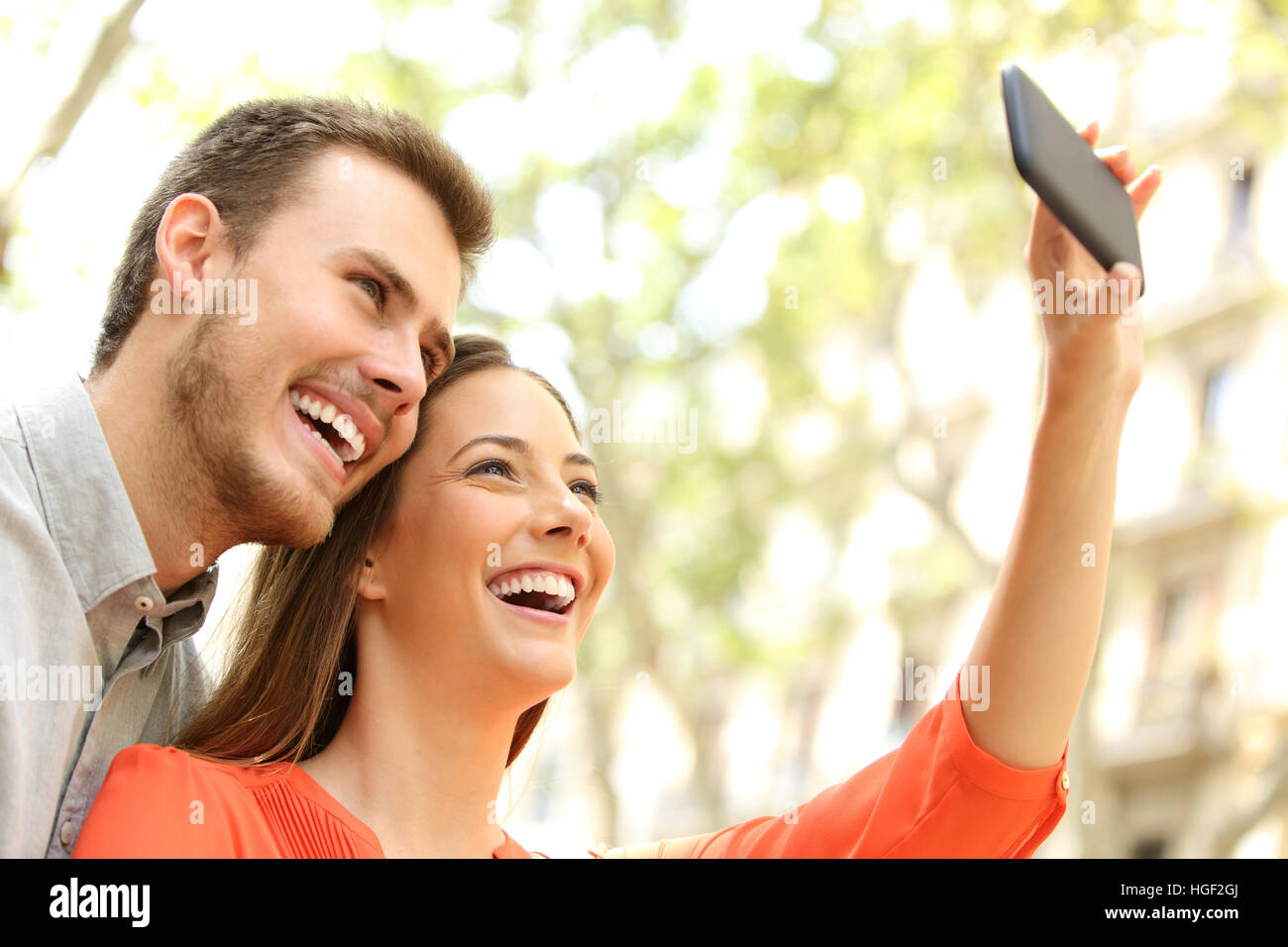 Happy casual couple taking selfie or photographing with a smart phone in the street - Stock Image