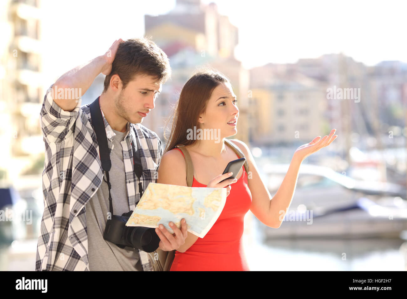Lost couple of tourists searching location in a guide and smart phone with a port in the background - Stock Image