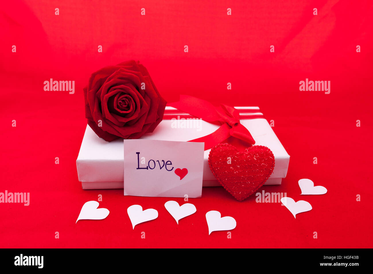 Valentines gift box with a red bow on red background. Image of Valentines day. Stock Photo