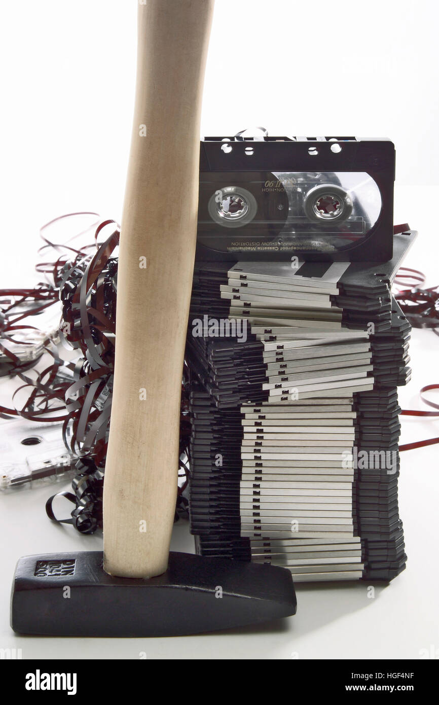 Hammer in front of a stack of floppy disks and an audio tape, jammed cassette tape in background - Stock Image