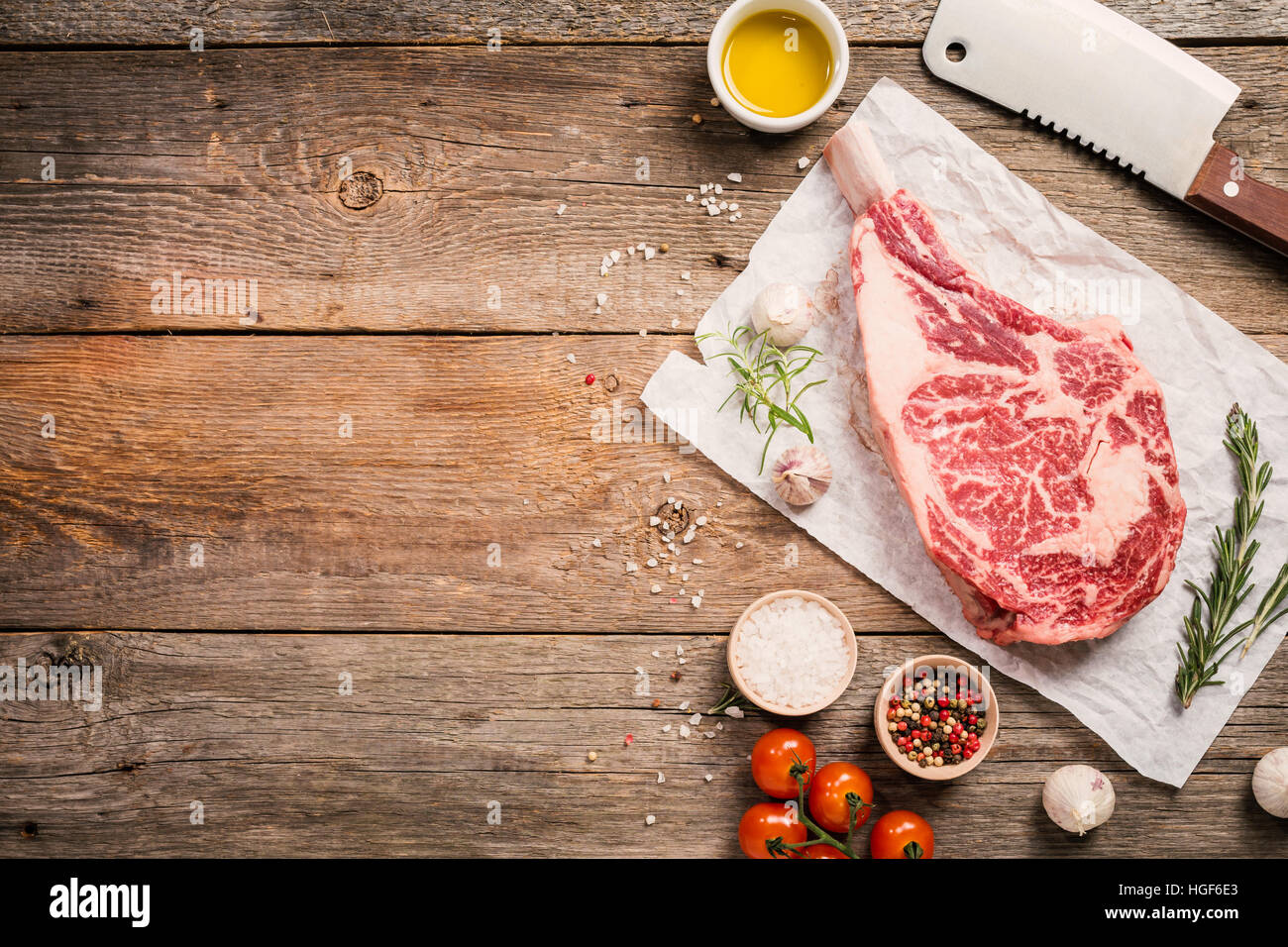 Raw tomahawk beef steak with ingredients for grilling: seasoning, fresh rosemary and olive oil on wooden background, - Stock Image