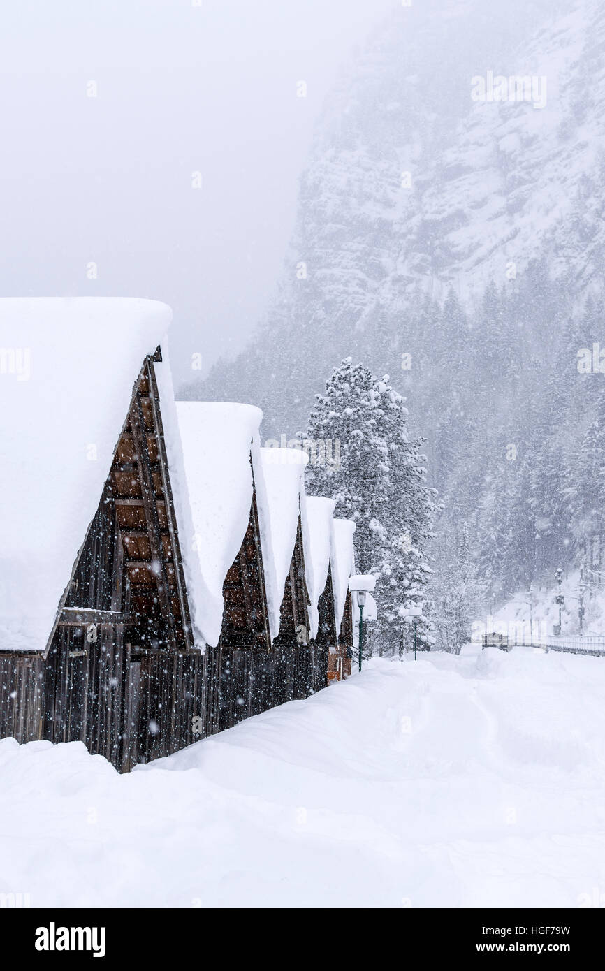 Wooden Mountain Houses in Winter Forest While Snowing. Winter Idyll. - Stock Image