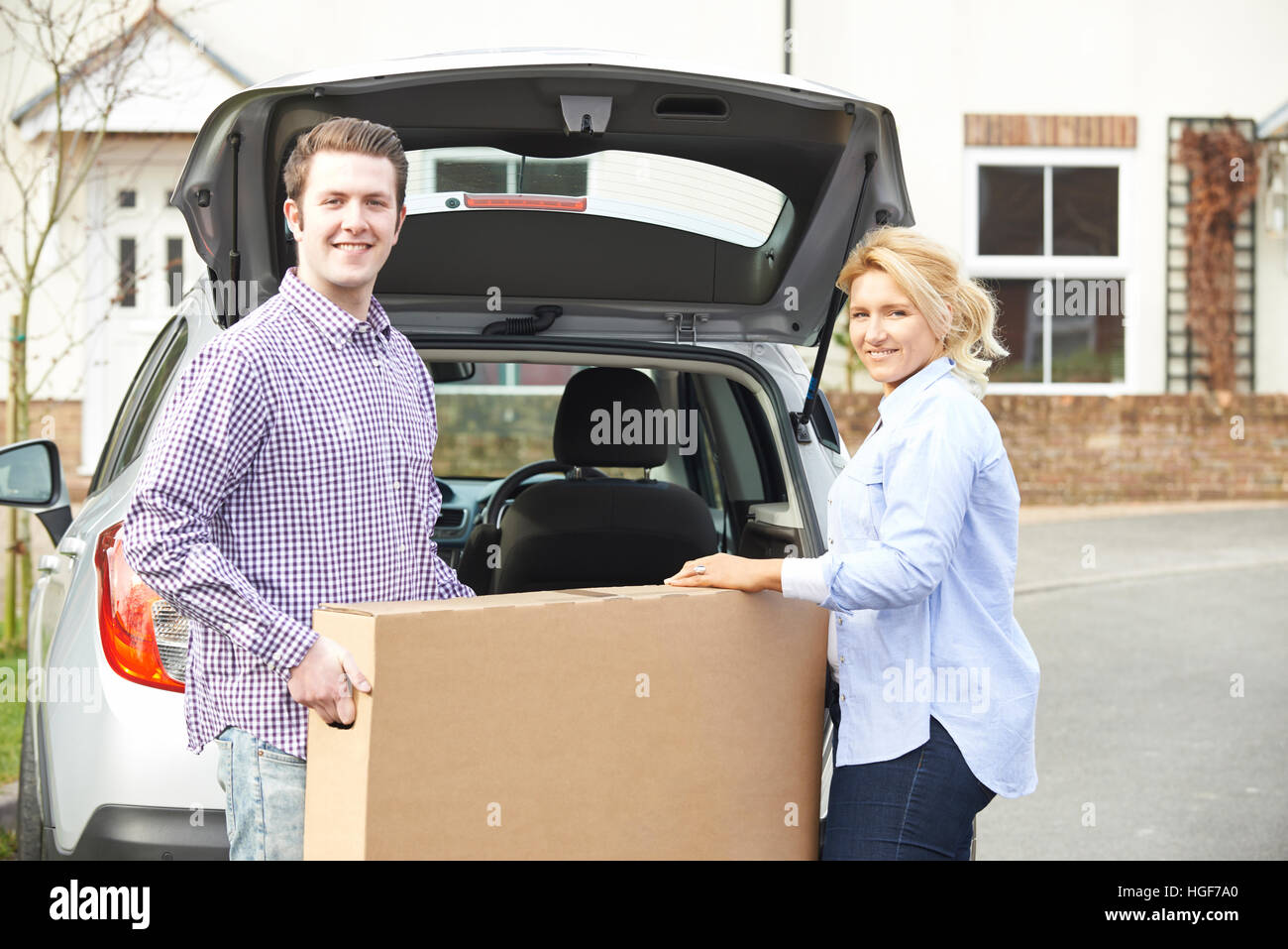 Couple Unloading New Television From Car Trunk - Stock Image