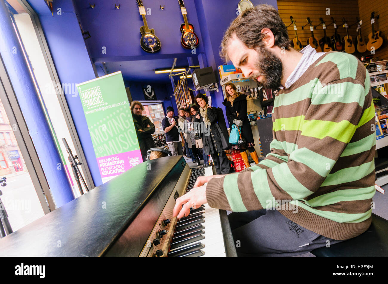 Pianist Matthew Bourne plays an old Fender Rhodes electronic keyboard in a music shop. - Stock Image