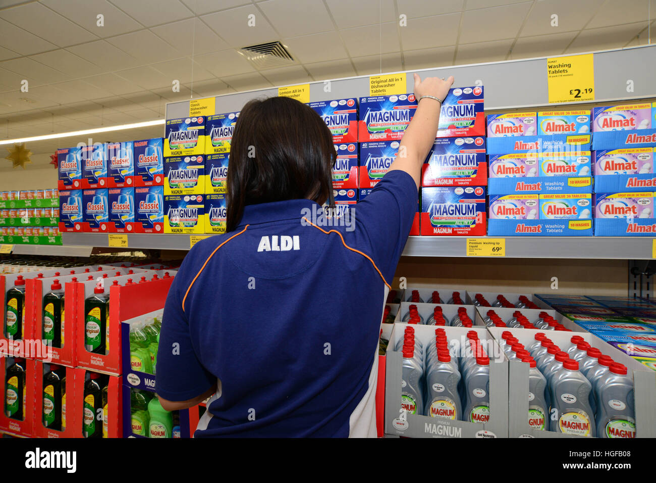 A store assistant stocking shelves in Aldi supermarket. - Stock Image