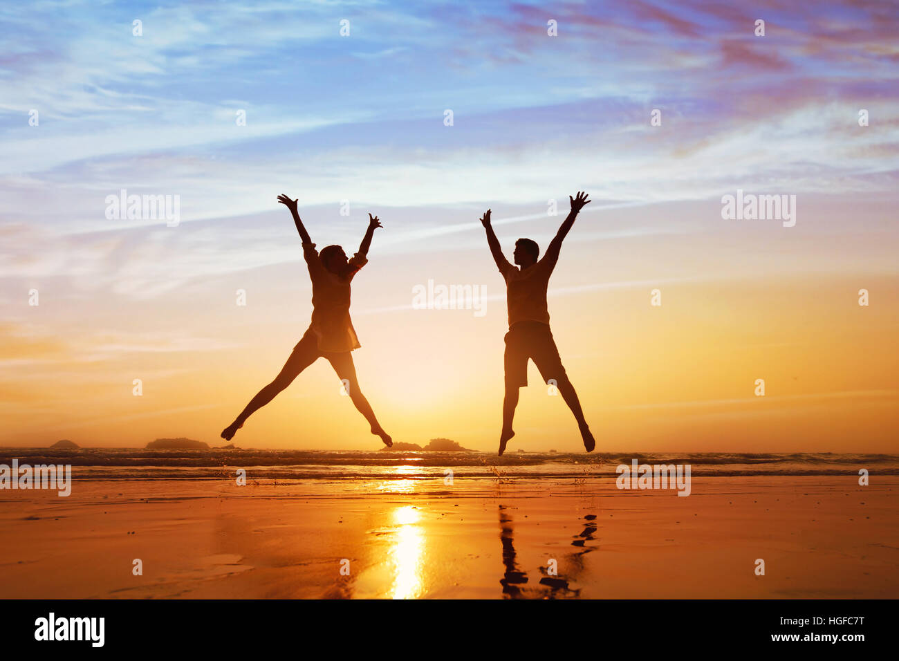 happy couple jumping on the beach at sunset, family summer holidays or honeymoon - Stock Image