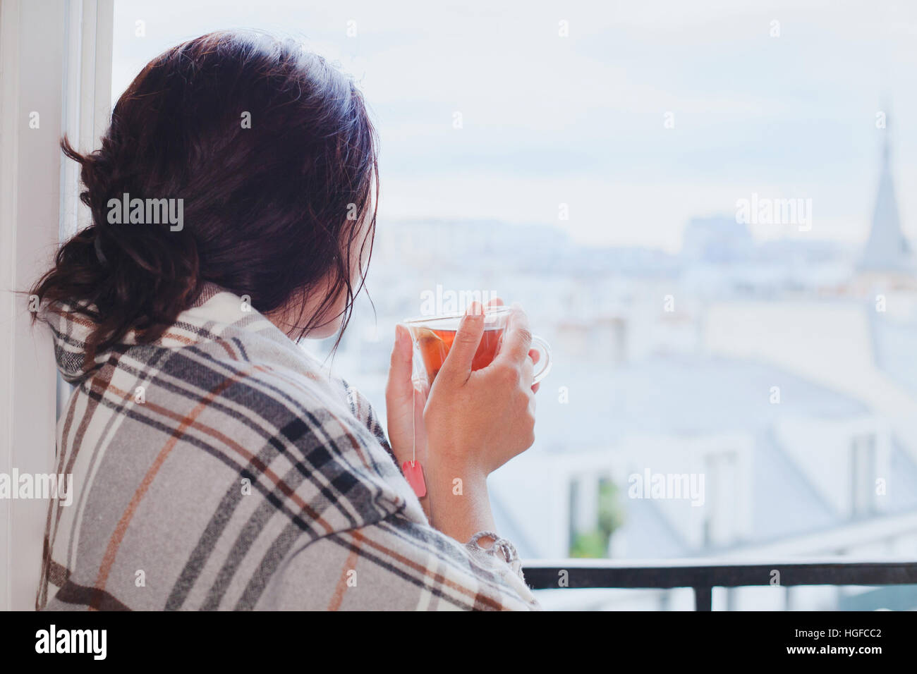 woman drinking hot tea and looking at the window, cozy winter at home, warm up, december in city, waiting - Stock Image