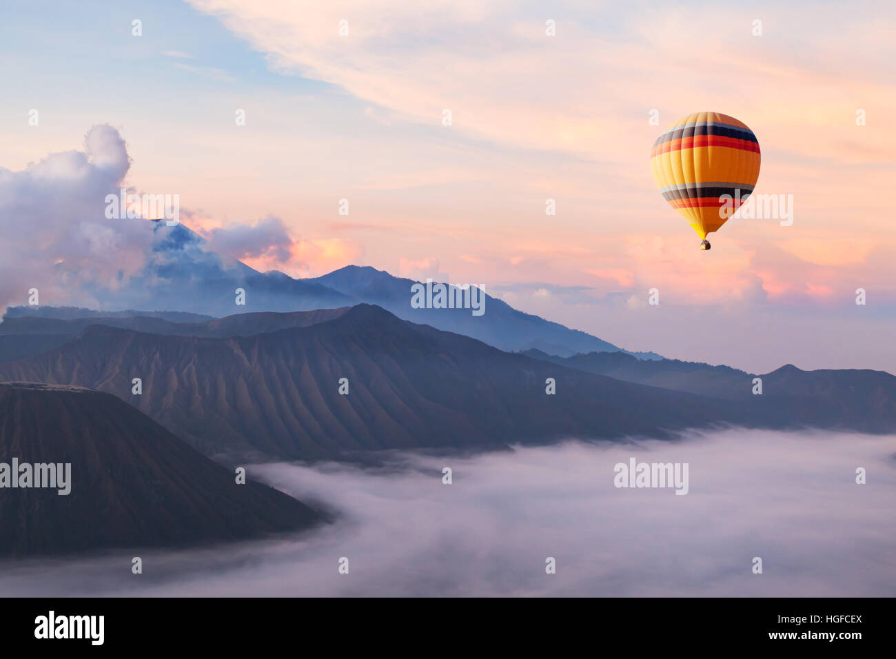 beautiful inspirational landscape with hot air balloon flying in the sky, travel destination - Stock Image