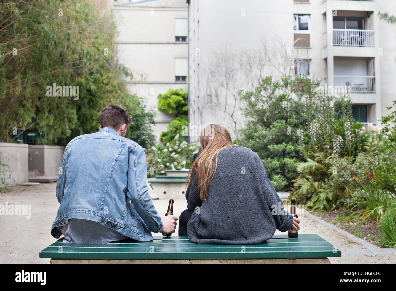 alcoholism, young people drinking beer on the bench - Stock Image