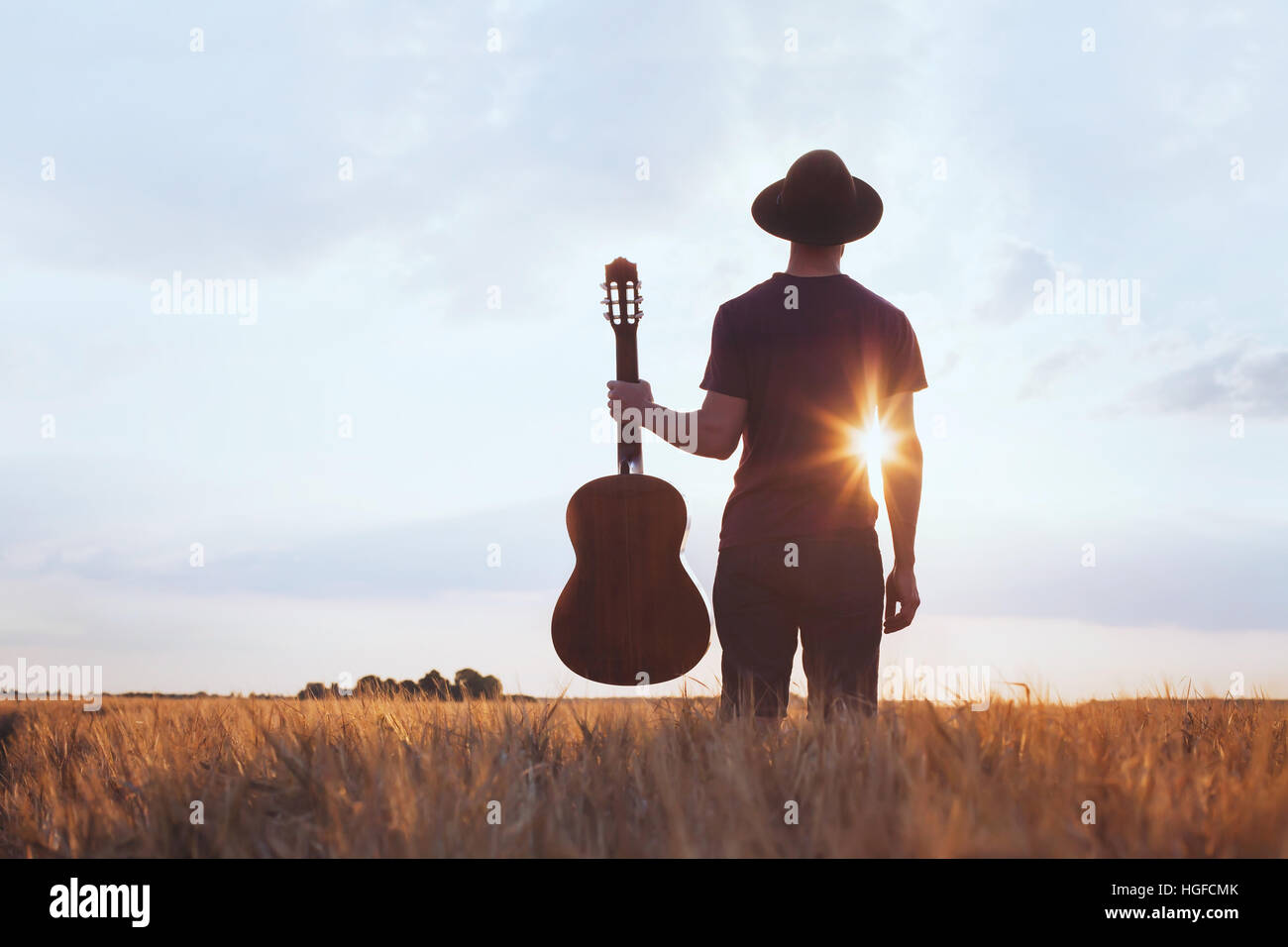 music festival background, silhouette of musician artist with acoustic guitar at sunset field - Stock Image