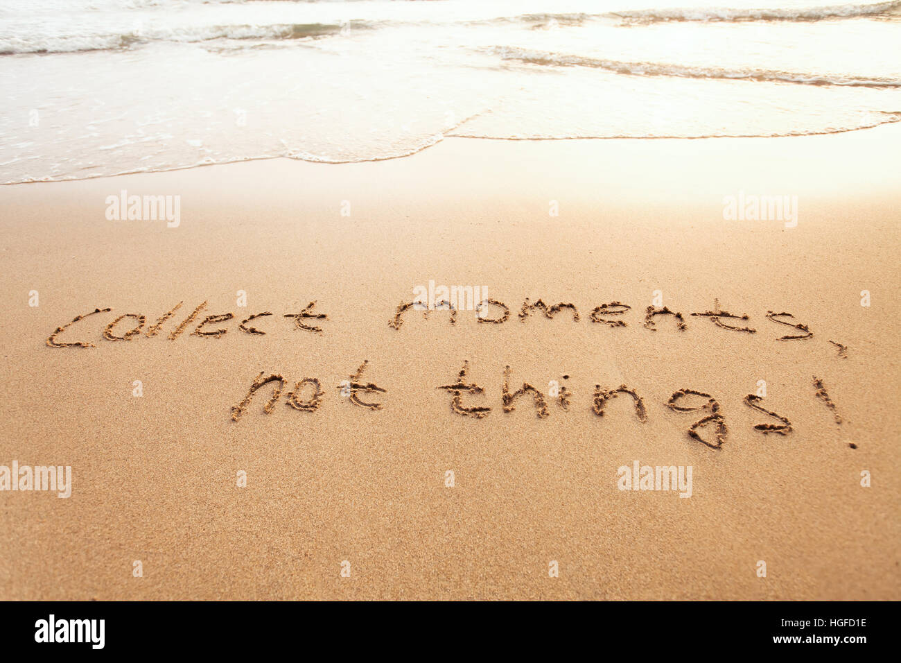 collect moments, not things - happiness concept, happy lifestyle inspirational quote, enjoy the life, text on sand Stock Photo