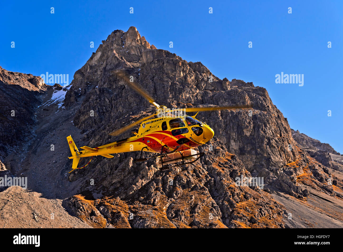 Helicopter Eurocopter AS350 Ecureuil of Heli Bernina AG operating in the Val Lischana, Engadin Alps, Graubunden, - Stock Image