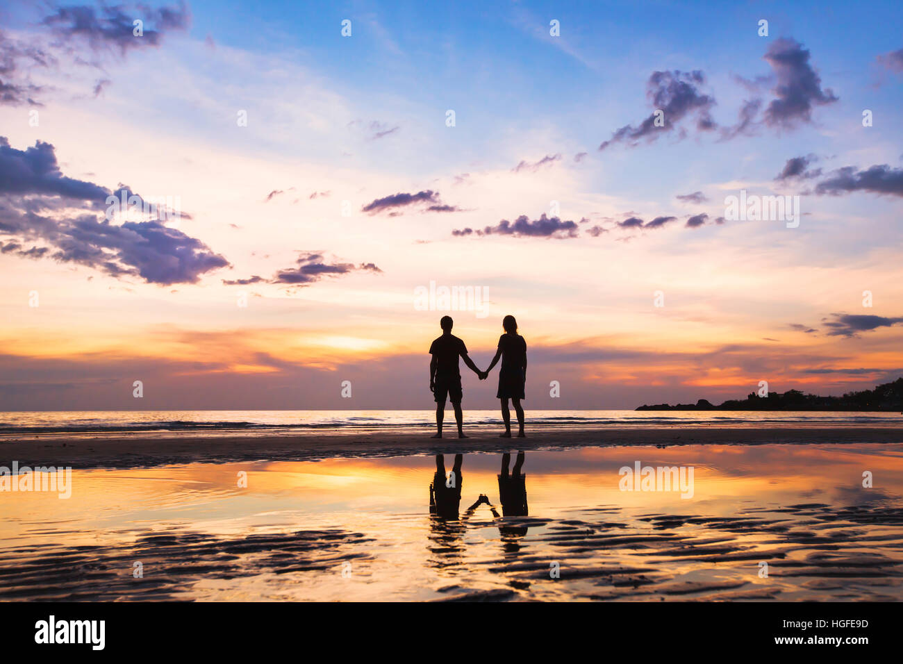 happy family on the beach, silhouette of couple at sunset, man and woman relationships, love - Stock Image
