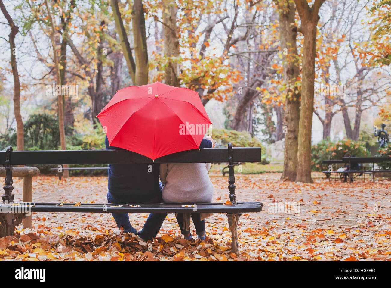 elderly retired couple sitting together on the bench in autumn park, love concept - Stock Image