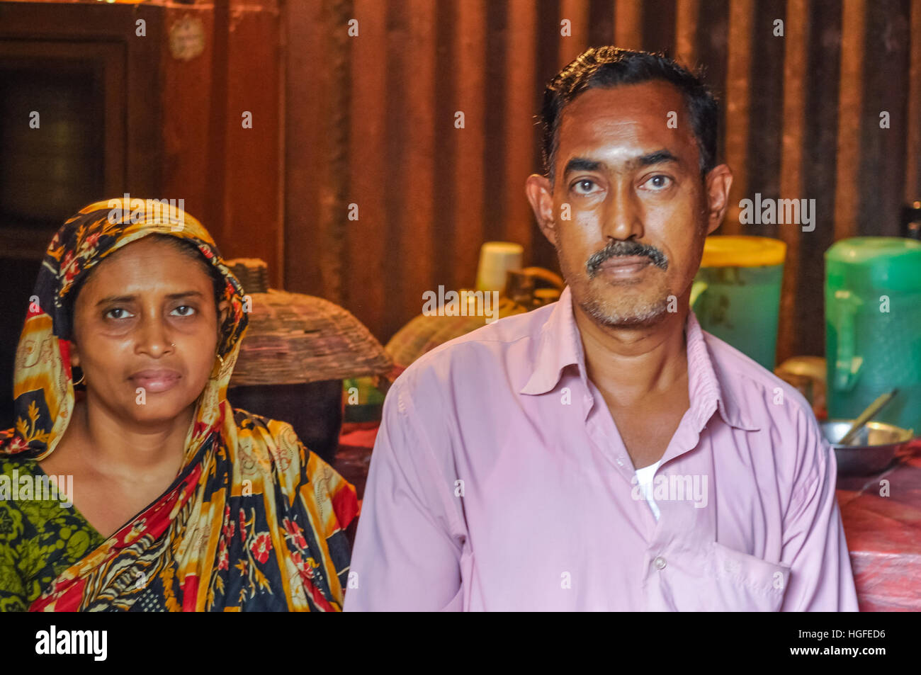Morolgang, Bangladesh - circa July 2012: Black-haired man with moustache dressed in pink shirt with his wife with - Stock Image