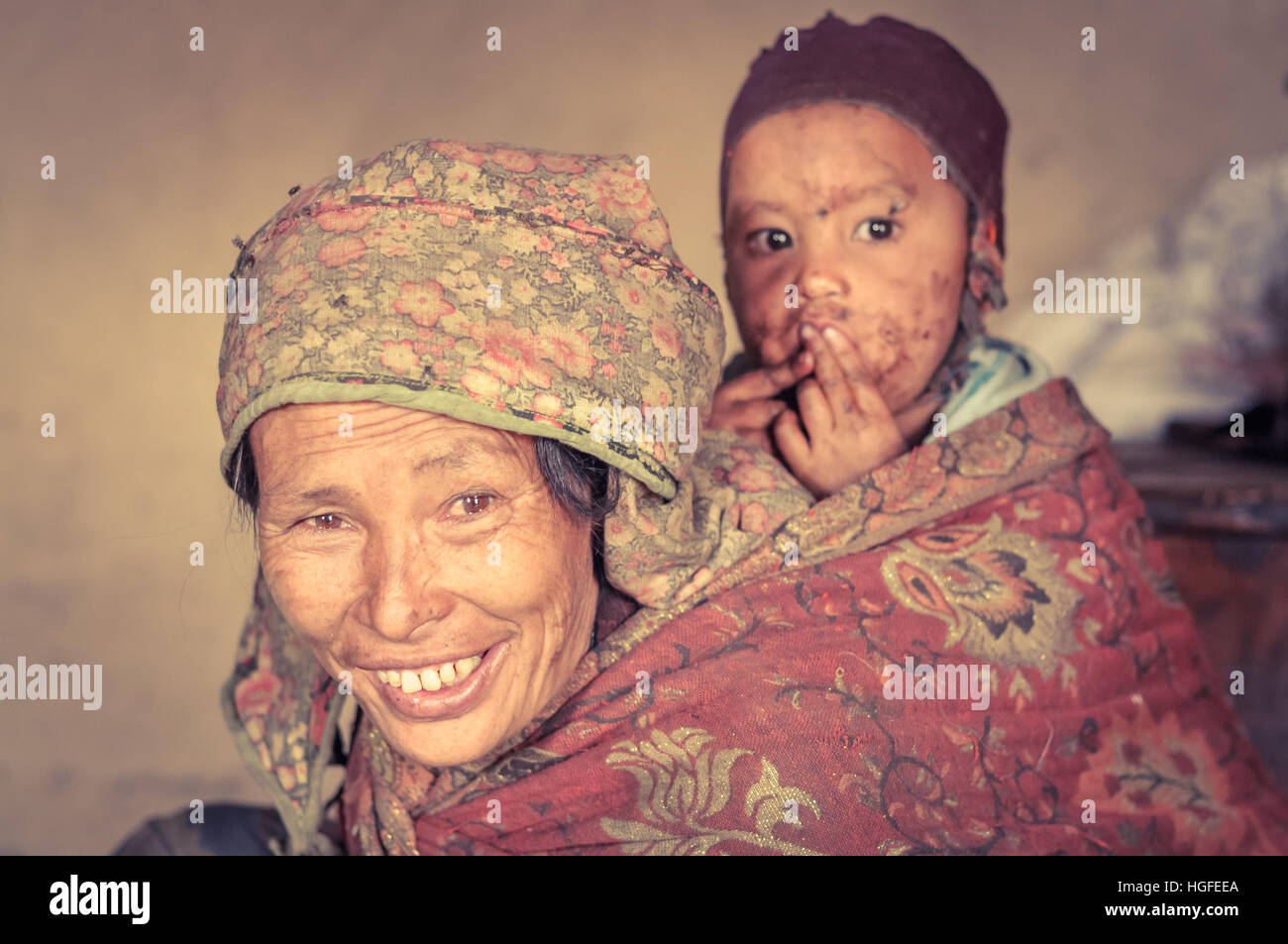 Dolpo, Nepal - circa May 2012: Photo of native brown-eyed woman in headcloth carrying child with brown cap on her - Stock Image