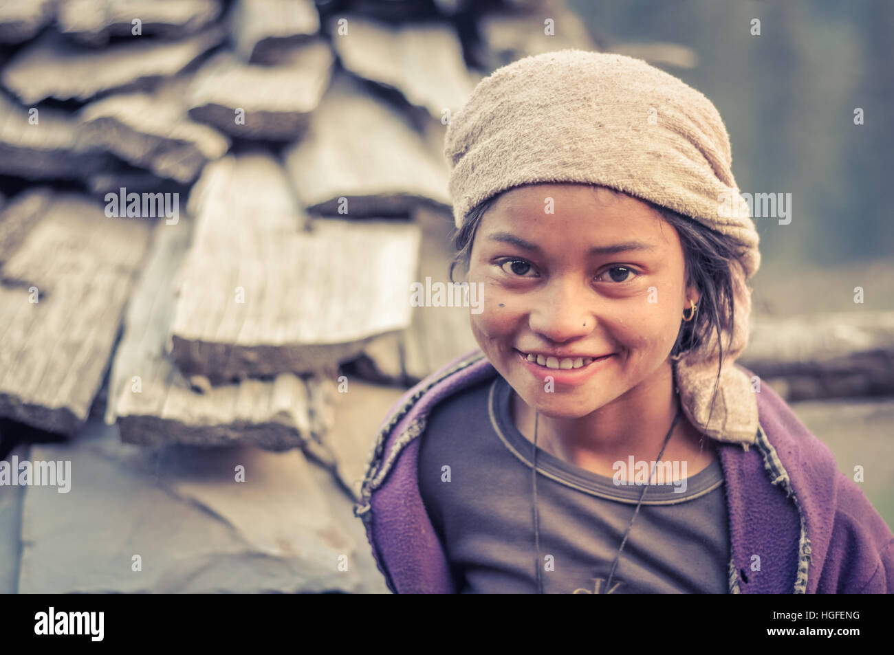 Dolpo, Nepal - circa May 2012: Young girl with beautiful big brown eyes wears headcloth and violet sweatshirt in - Stock Image
