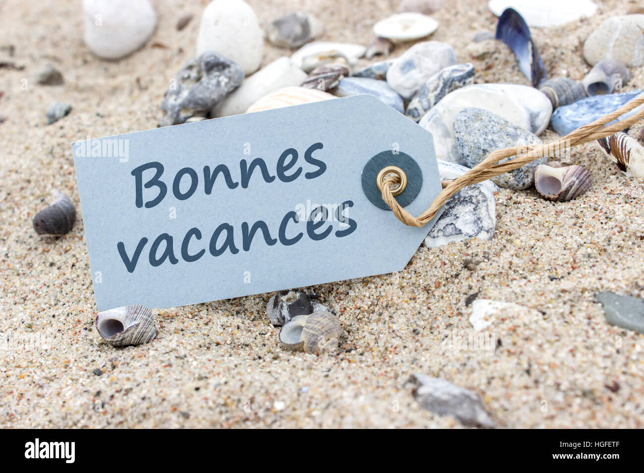 Card with French words 'Nice Vacations' in beach sand - Stock Image