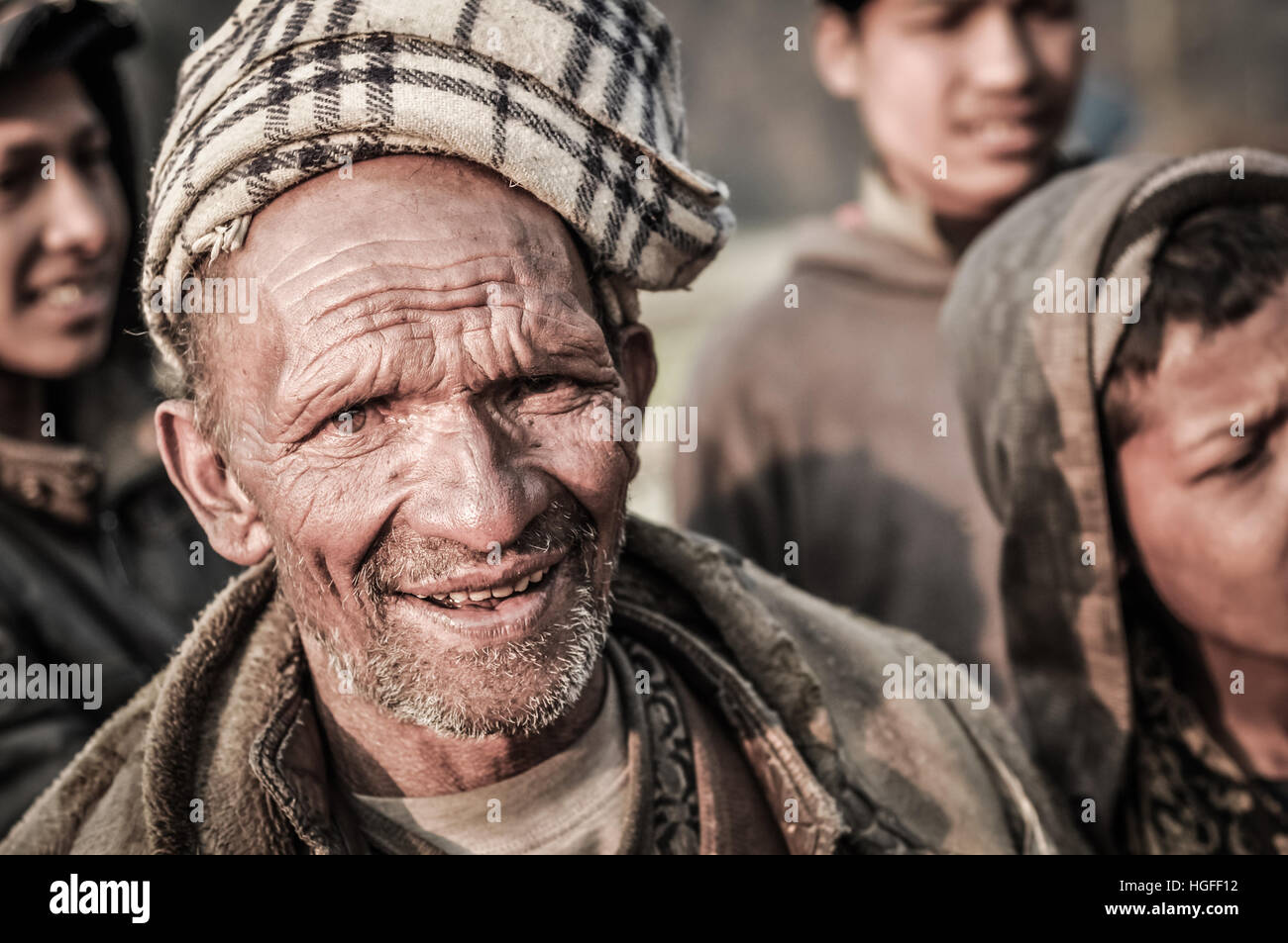 Dolpo, Nepal - circa May 2012: Old native man with little beard wears brown headcloth and jacket and frowns to photocamera - Stock Image