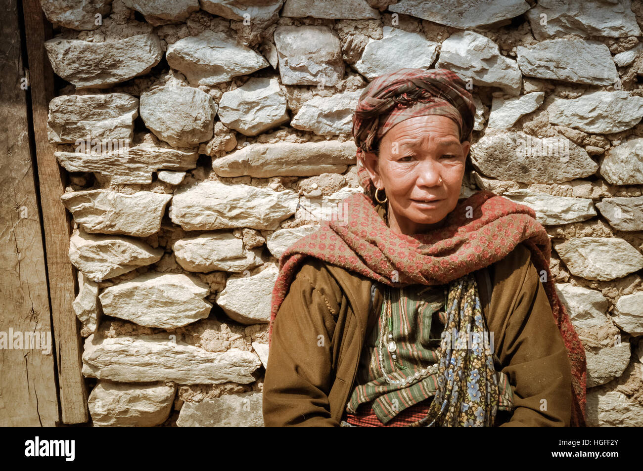 Dolpo, Nepal - circa May 2012: Native woman with red headcloth and scarf wears brown jacket and sits in front of - Stock Image