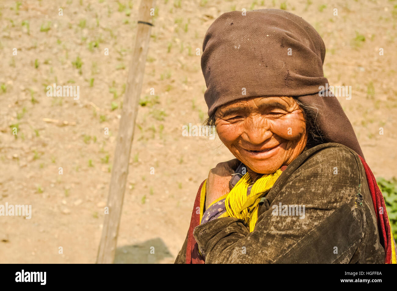 Dolpo, Nepal - circa May 2012: Old native woman with wrinkled face and brown headcloth looks down and smiles nicely - Stock Image