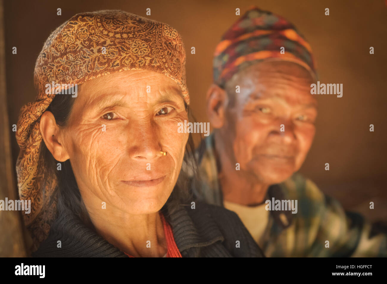 Beni, Nepal - circa May 2012: Native woman with headcloth and piercing in her nose with her husband in background Stock Photo