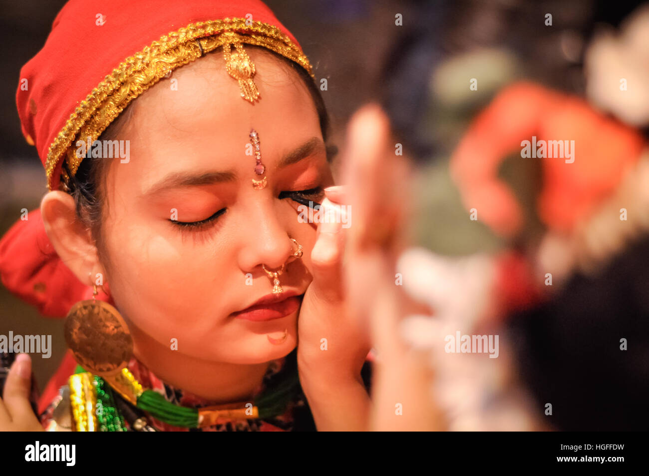 Guwahati, Assam - circa April 2012: Young native girl with red headcloth and earrings gets her eye lined by eye - Stock Image