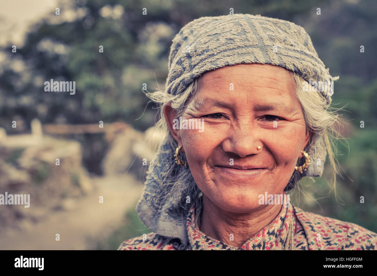 Beni, Nepal - circa May 2012: Native grey-haired woman with headcloth and golden earrings and piercing smiles nicely - Stock Image