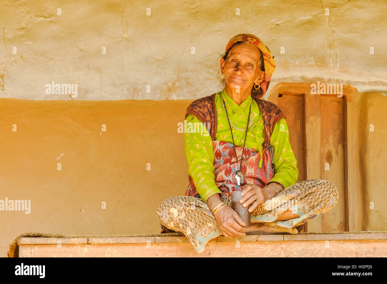 Beni, Nepal - circa May 2012: Old woman in yellow shirt with headcloth sits cross-legged on bench in Beni, Nepal. - Stock Image