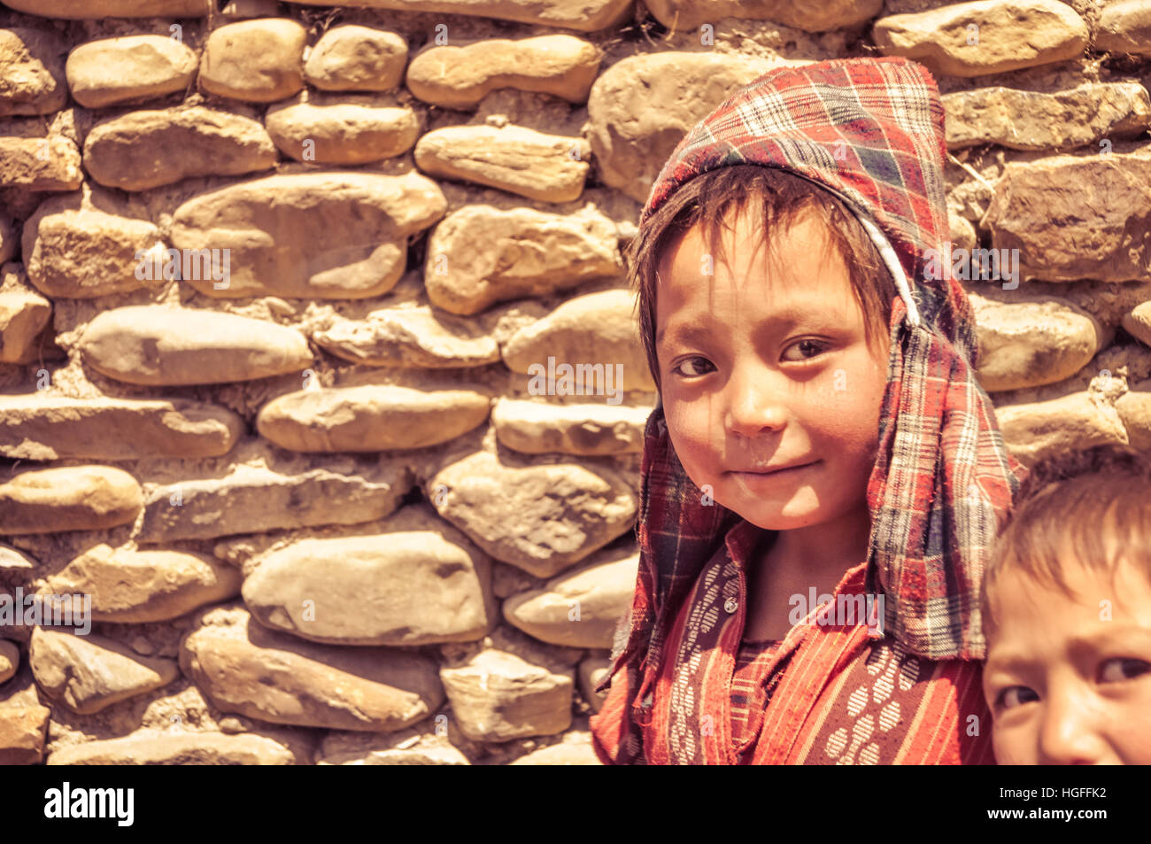 Dolpo, Nepal - circa June 2012: Small brown-haired boy with checked red headcloth and red shirt with nice brown - Stock Image