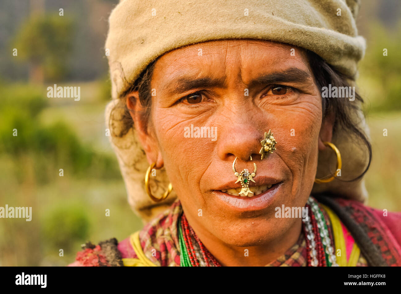 Dolpo, Nepal - circa May 2012: Native woman with brown headcloth has large earrings and piercings in her nose with - Stock Image