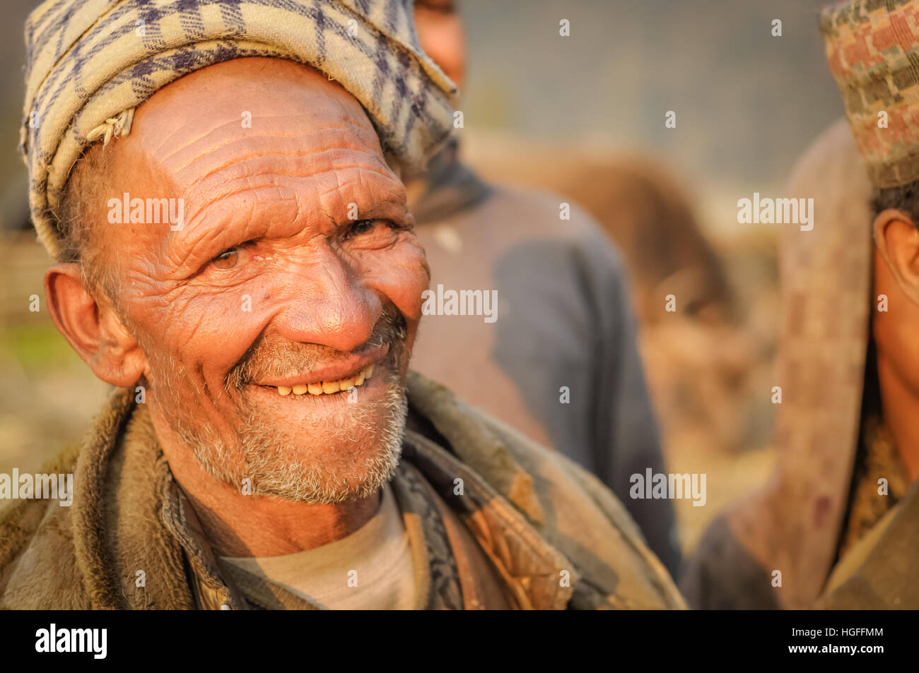 Dolpo, Nepal - circa May 2012: Old native man with little beard wears brown headcloth and jacket and bites his lip - Stock Image