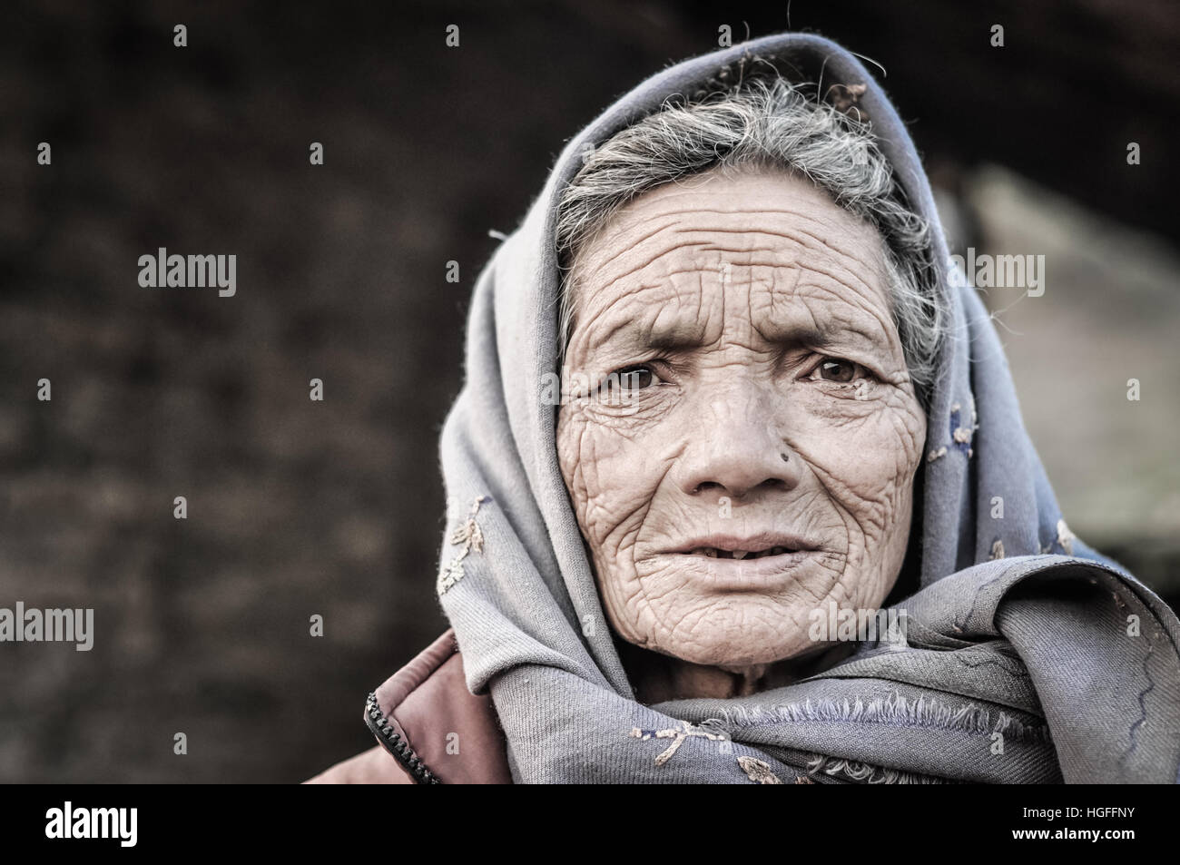 Dolpo, Nepal - circa May 2012: Old woman with wrinkles on her face and brown eyes wears grey headcloth in Dolpo, - Stock Image
