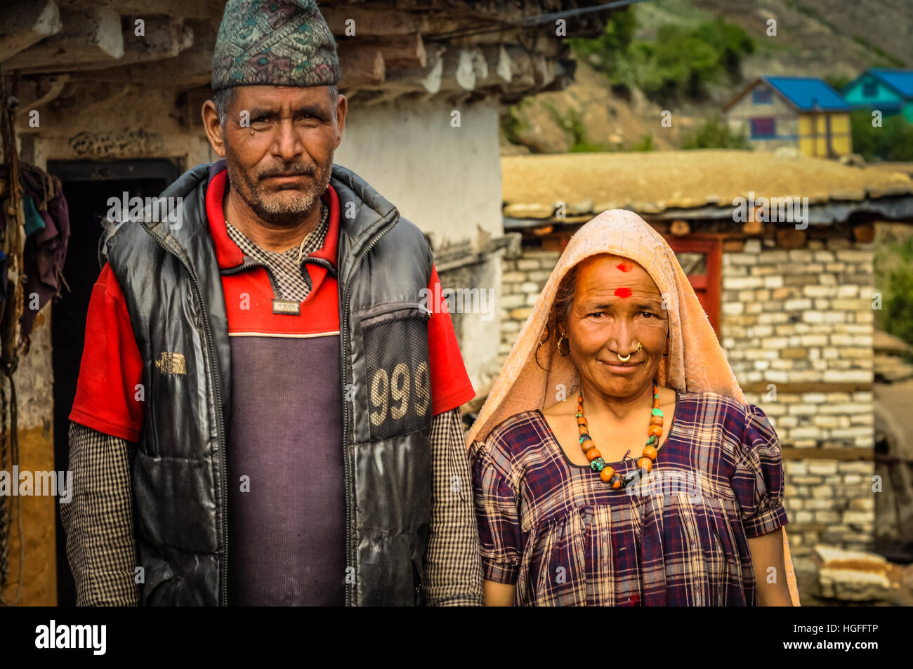 Dolpo, Nepal - circa June 2012: Native man with cap wears grey vest and red shirt with his wife in purple dress - Stock Image